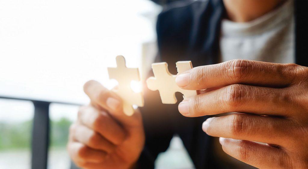 Hände mit Puzzleteilen